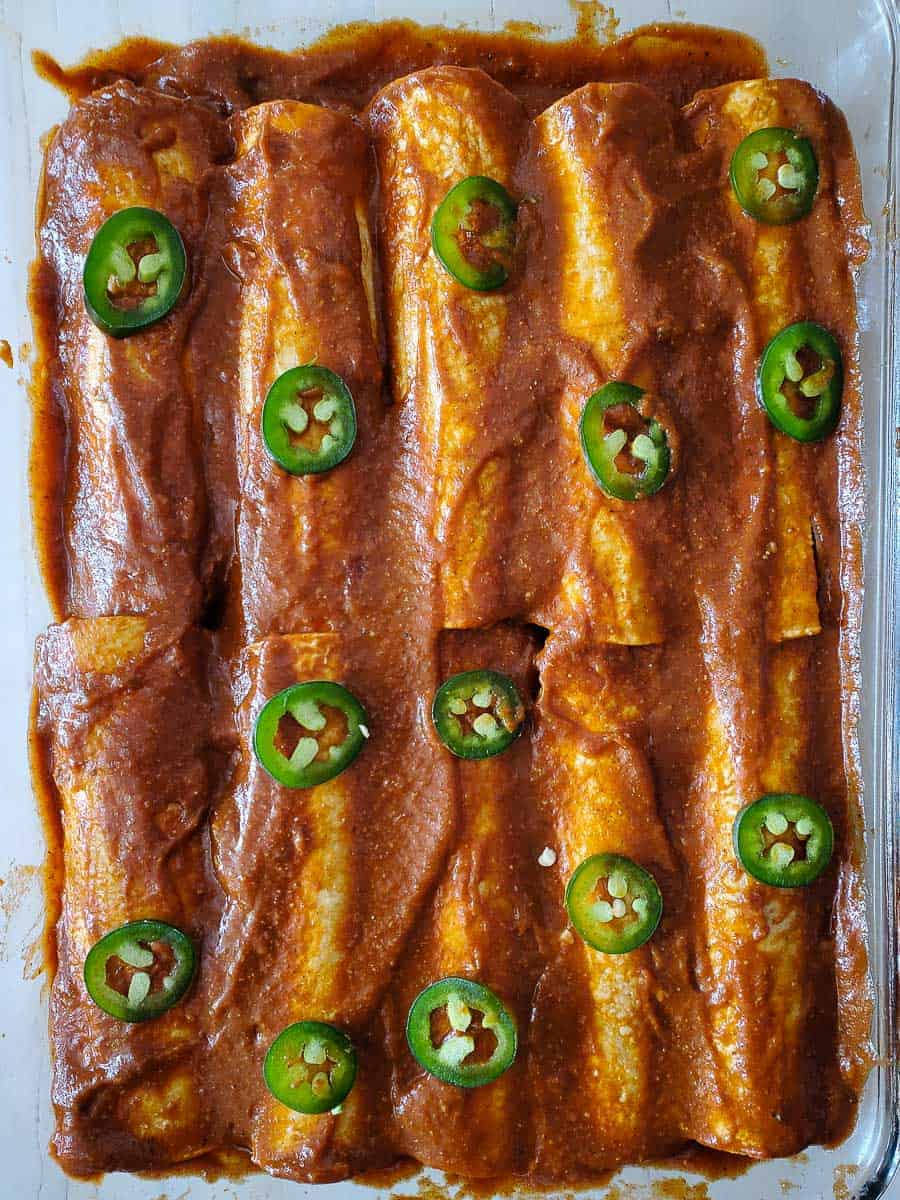Pan Of Enchiladas With Sauce And Jalapeño Slices