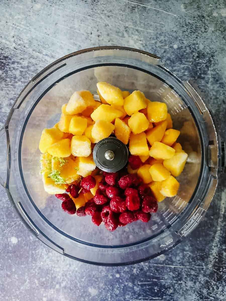 Mango Chunks, Lime Zest, Raspberries, And Coconut Milk In A Food Processor