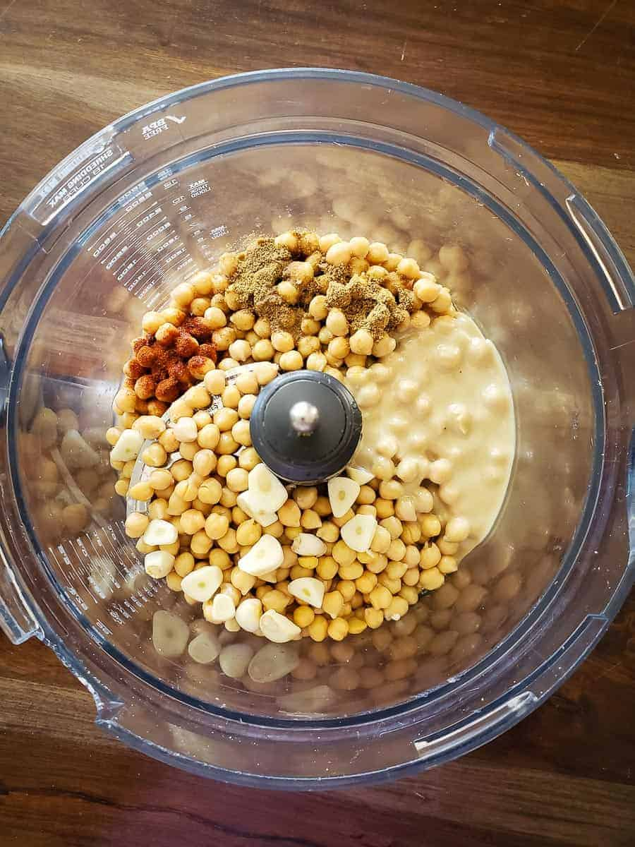 Garlic, tahini, aquafaba, fresh spices, and chickpeas in a food processor