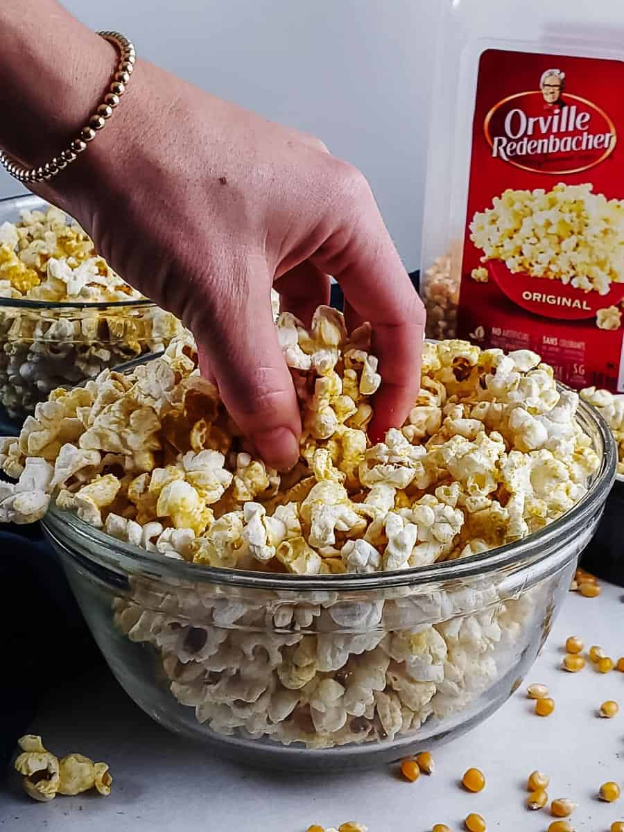 Hand Reaching Into A Bowl Of Popcorn