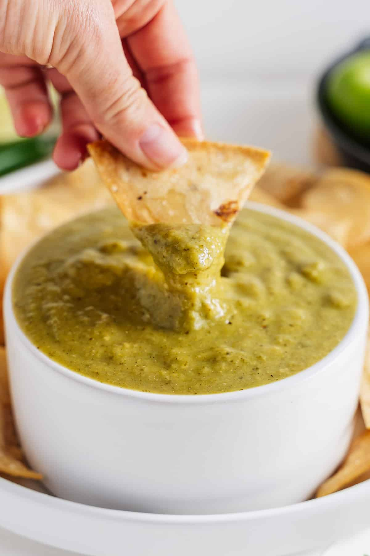 Hand Dipping Chip in Salsa Verde