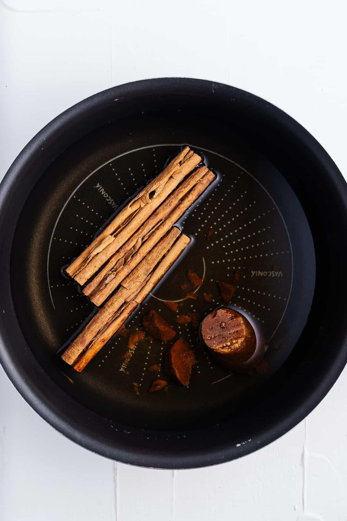Cinnamon Sticks, Piloncillo, and Water in a Pot