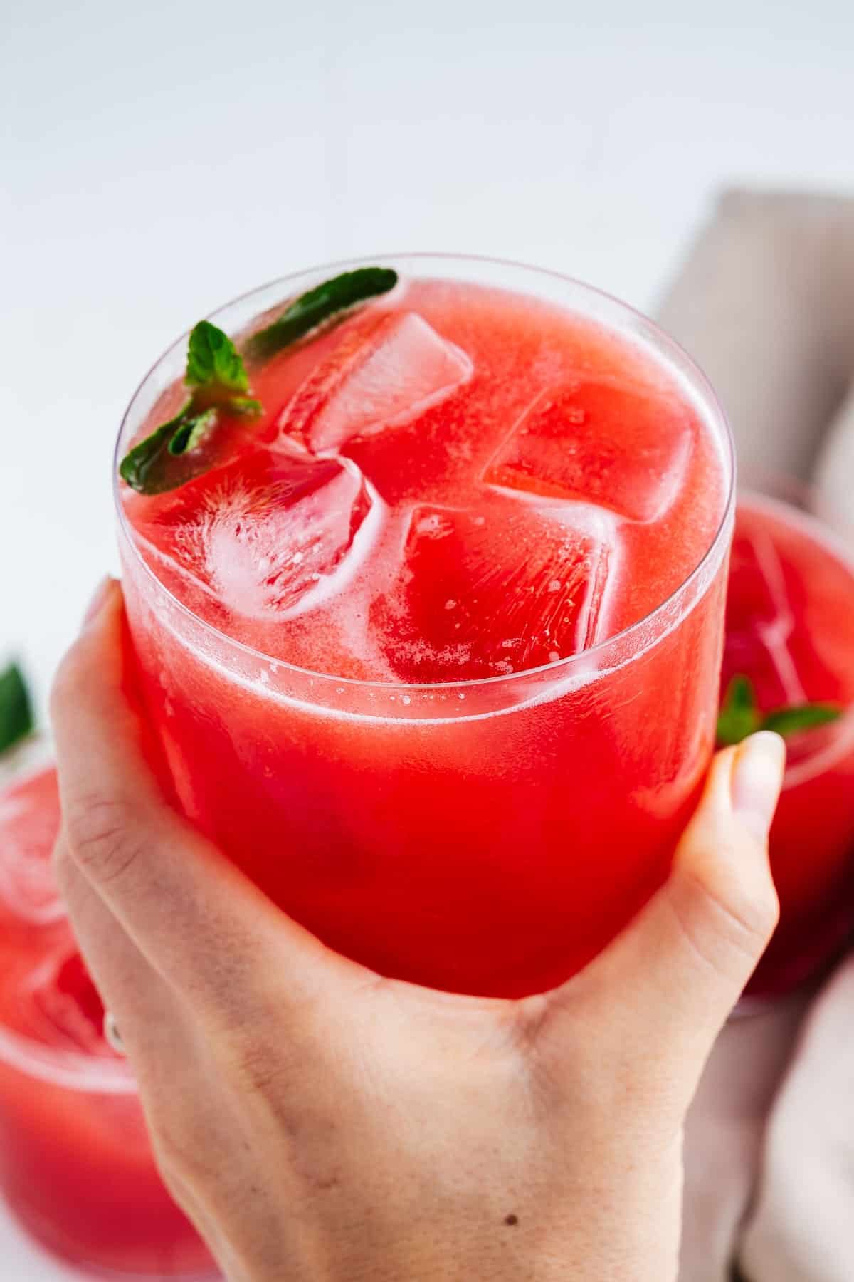 Hand Holding a Glass of Agua de Sandia