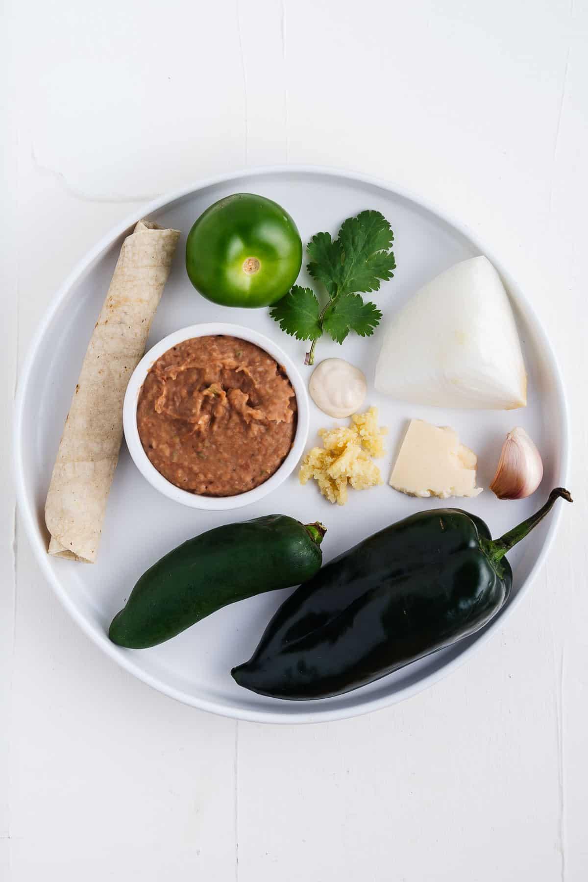 Green Chiles, Refried Beans, Tortilla, Tomatillo, Cilantro, Onion, Garlic, Vegan Cheese, and Mexican Crema