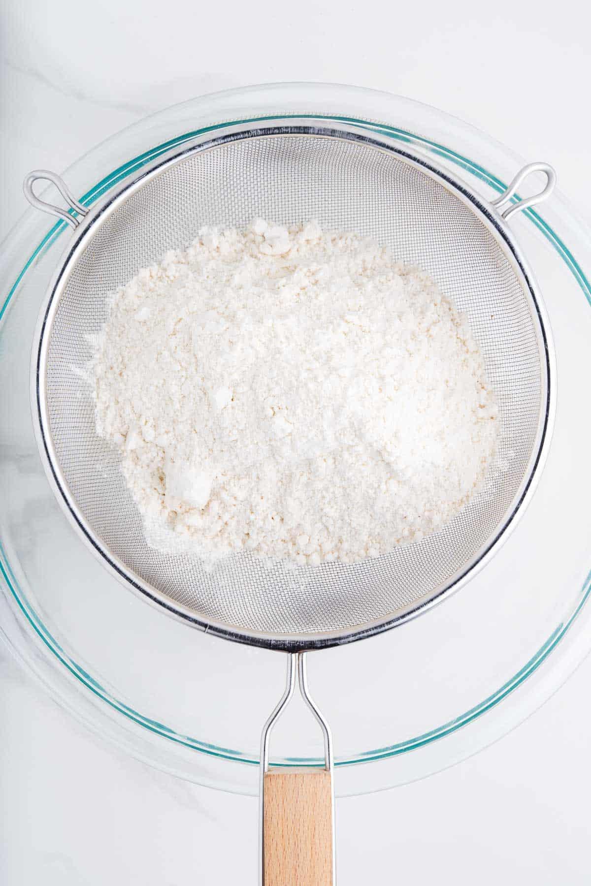 Flour Sifting Through a Strainer into a Bowl