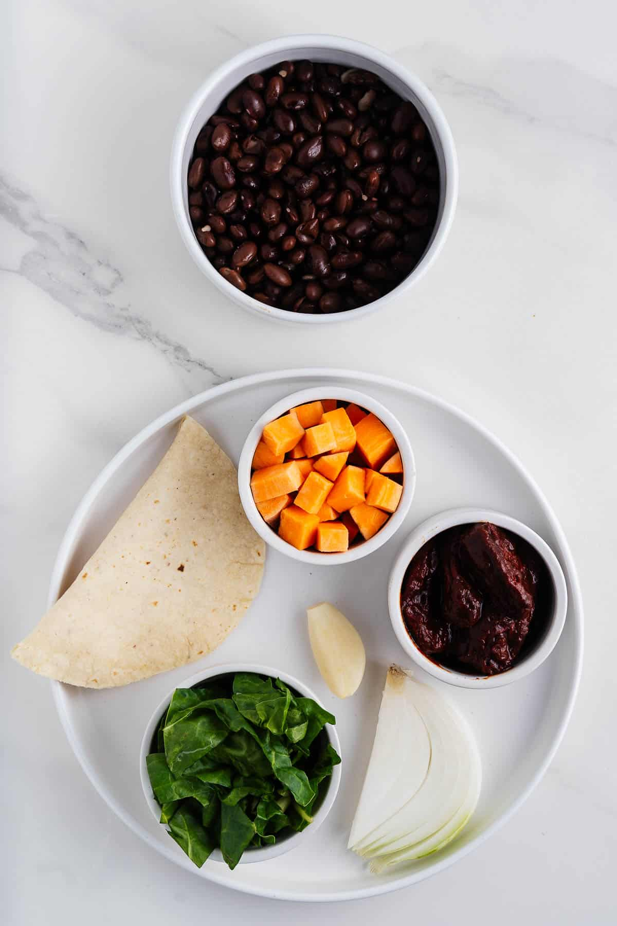 Black Beans, Sweet Potatoes, Collard Greens, Chipotle Peppers in Adobo, Corn Tortilla, Garlic Clove, and White Onion