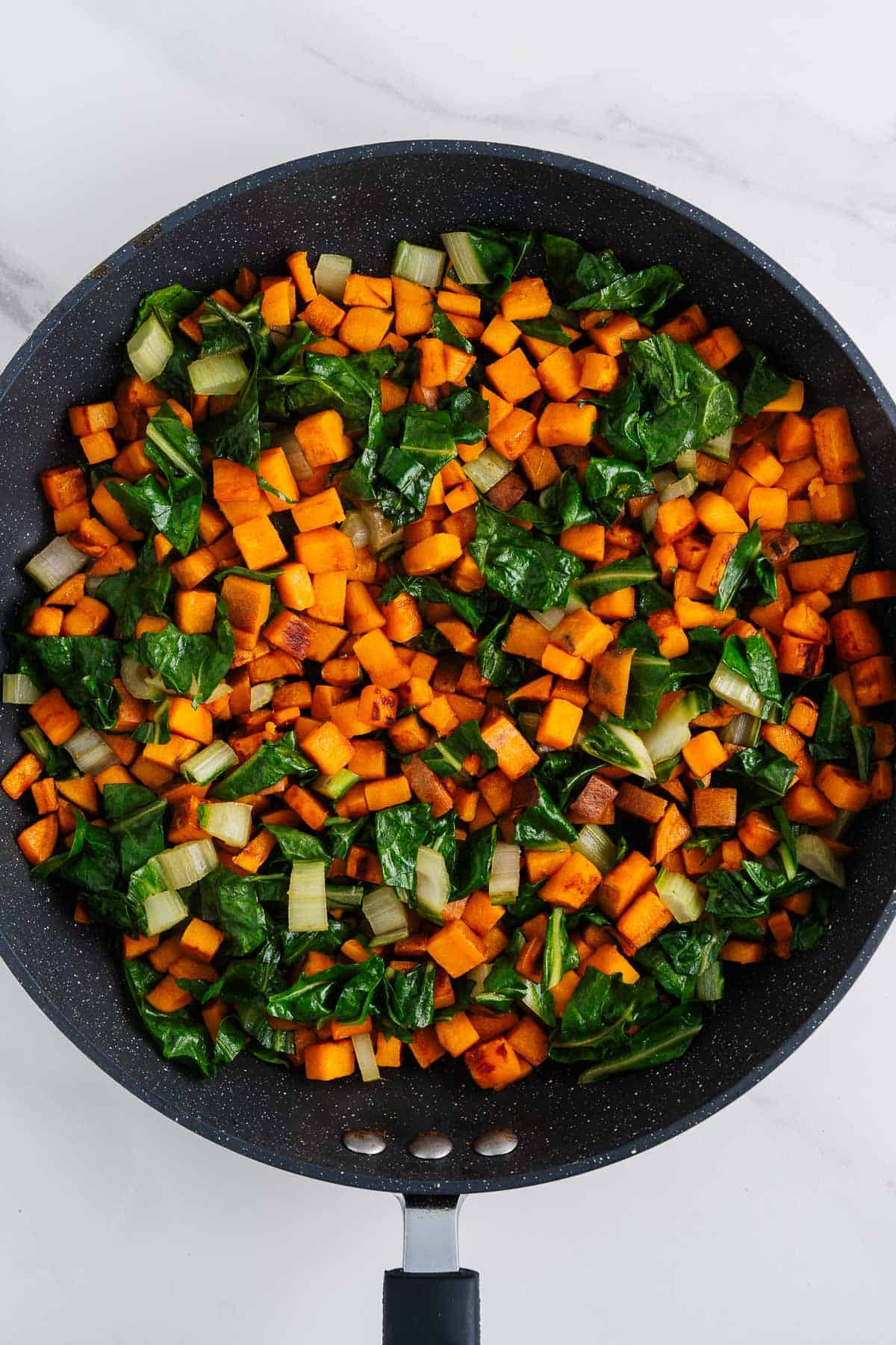Cooked Sweet Potatoes and Collard Greens in a Skillet