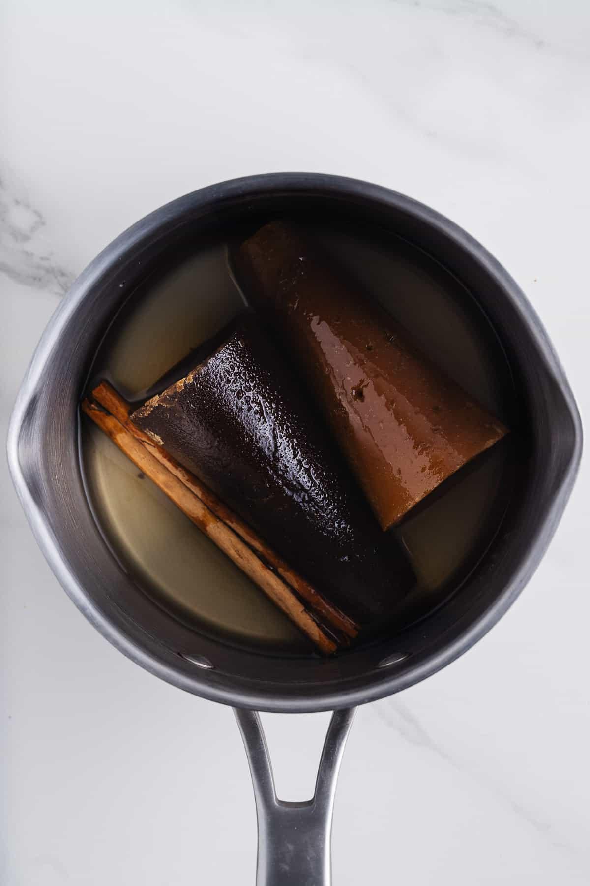 Piloncillo Cones, Cinnamon Stick, and Water in a Saucepan