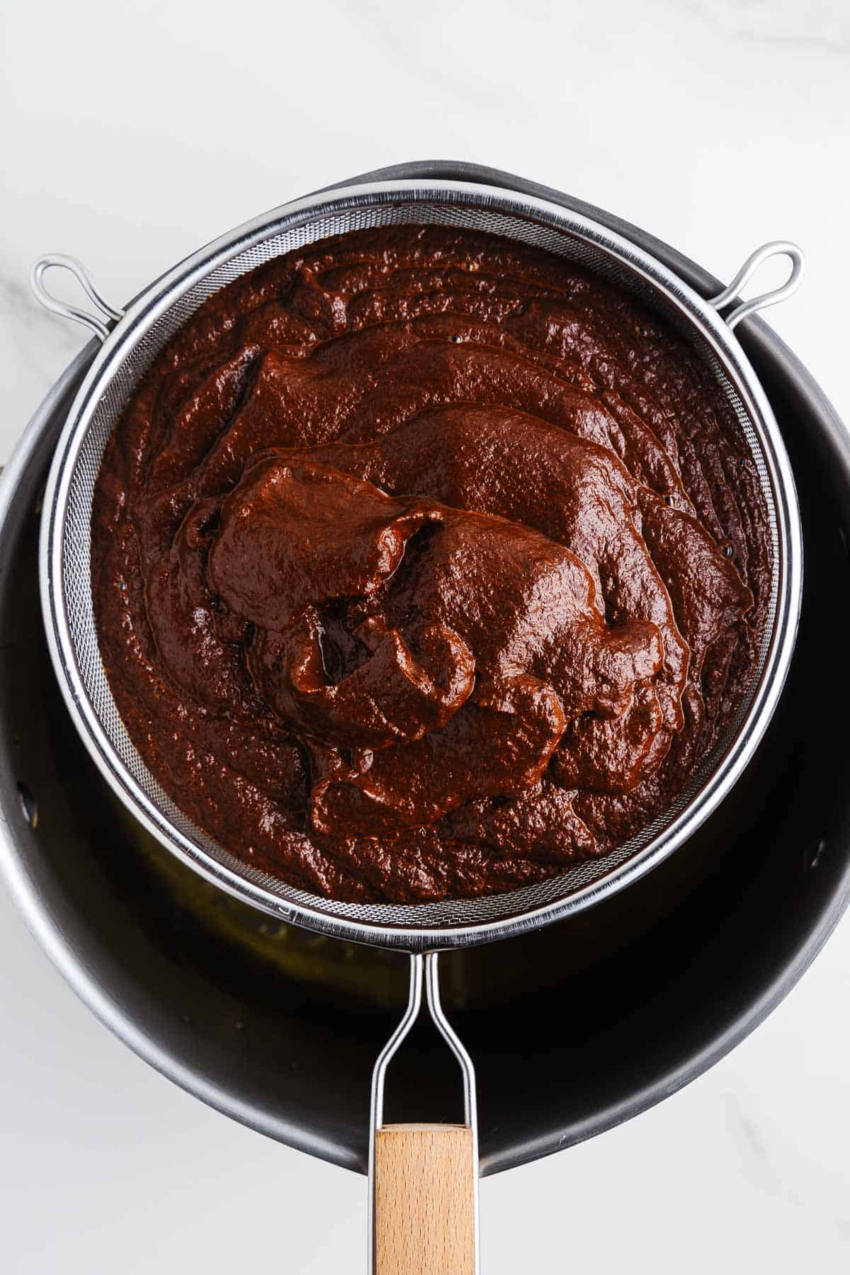 Mole Paste in a Strainer Over a Pot