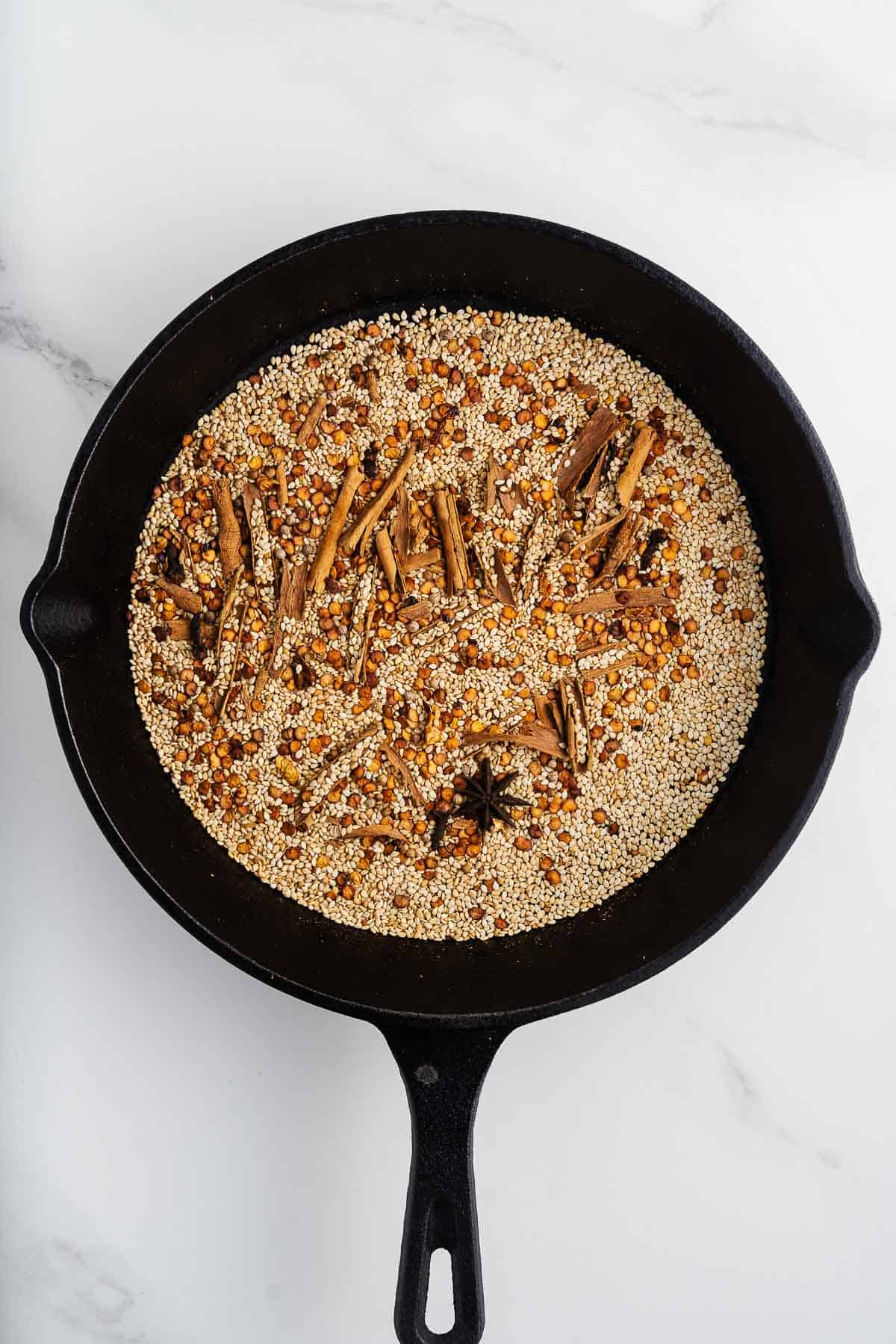 Toaste Spices, Sesame Seeds, and Chile Seeds in a Skillet