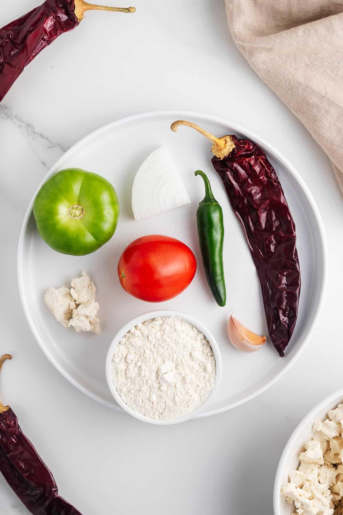 Tomato, Tomatillo, Guajillo Chile, Serrano Chile, Masa Harina, Garlic, Queso Fresco, and Onion