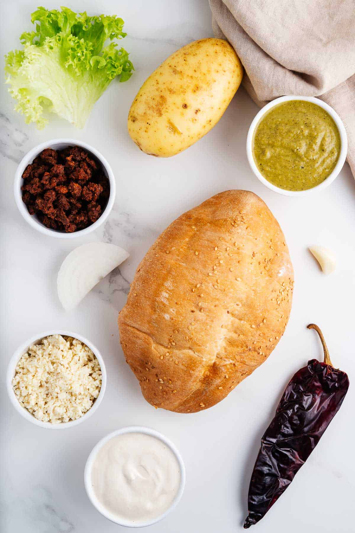 Bun, Potato, Lettuce, Chile, Cotija, Crema, Onion, Garlic, Salsa Verde, and Vegan Chorizo