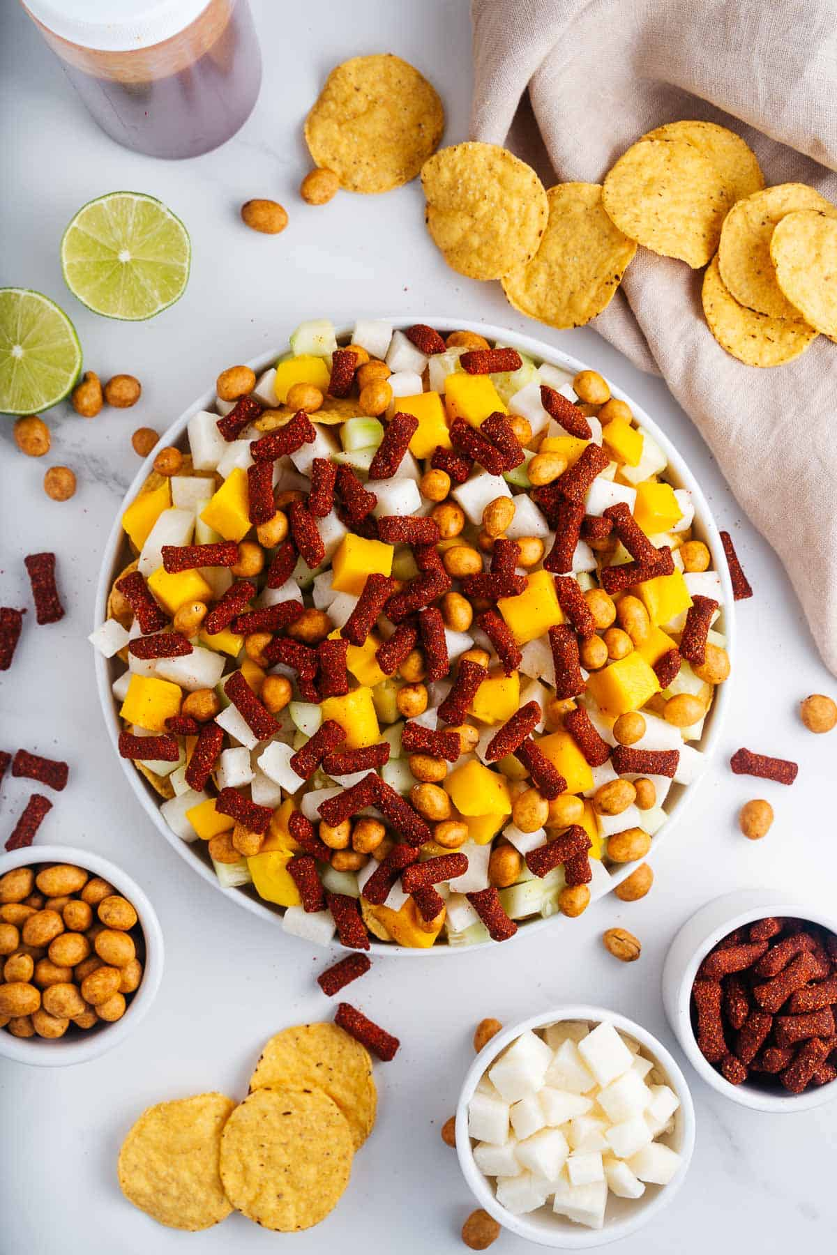 Plate of Tortilla Chips With Jicama, Cucumber, Mango, Tamarind Candies, and Cracker Nuts on Top