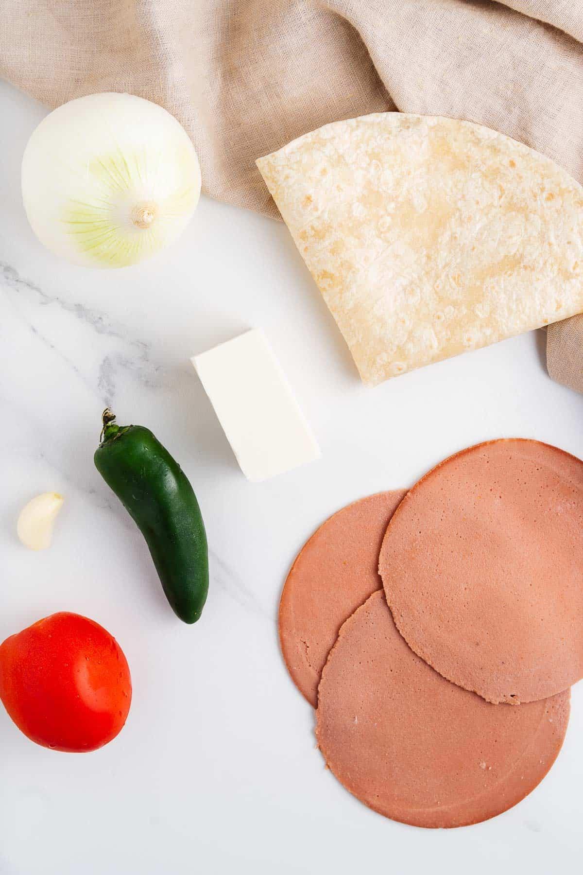 Vegan Cheese, Vegan Ham, Jalapeño, Tomato, Garlic, Onion, and Flour Tortilla