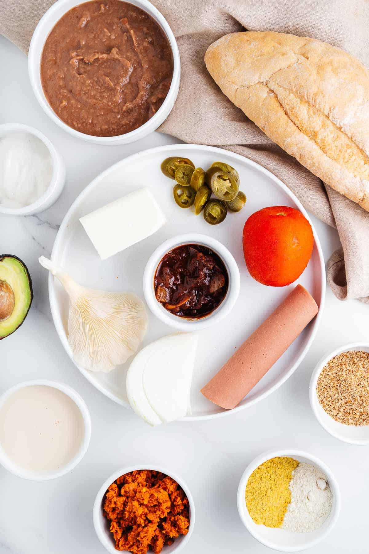 Vegetables, Oyster Mushroom, Refried Beans, Vegan Ham, Spices, Bolillo Bread, Mayo, Avocado, Soy Milk, and Vegan Chorizo