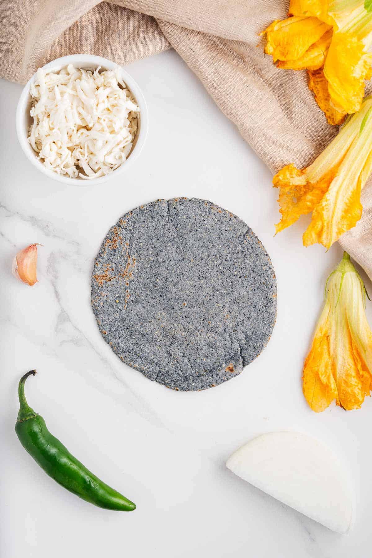 Blue Corn Tortilla, Squash Blossom, Serrano, Garlic, Onion, and Vegan Cheese