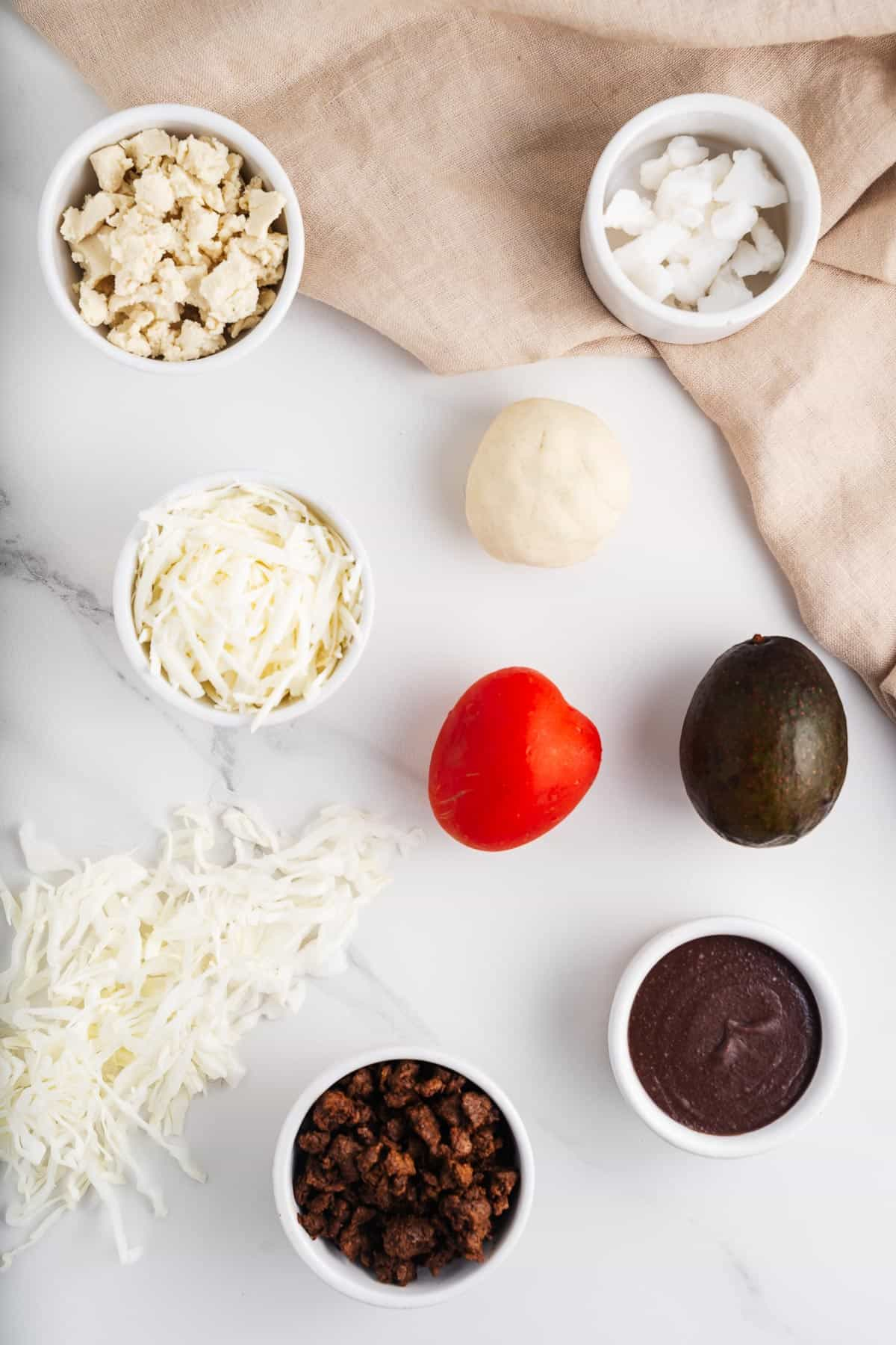 Vegan Mozzarella, Queso Fresco, Tomato, Masa, Avocado, Cabbage, Vegetable Shortening, Refried Beans, and Chorizo